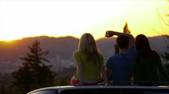 3 Teens Sit On Car And Watch The Sunset Together Stock Footage