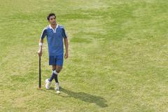 Man holding a hockey stick in a field - stock photo