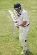 Cricket batsman playing a defensive stroke Stock Photos