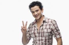 Portrait of a man showing victory sign Stock Photos