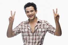 Portrait of a man gesturing victory sign - stock photo