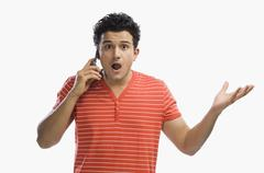 Man talking on a mobile phone and looking shocked Stock Photos