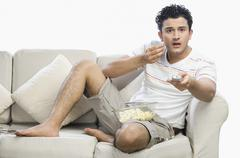 Man watching television and looking surprised - stock photo