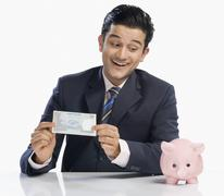 Businessman holding a currency note and looking at a piggy bank - stock photo