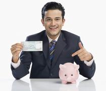 Businessman holding a currency note and pointing at a piggy bank - stock photo