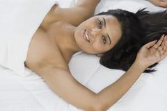 High angle view of a woman lying on the bed - stock photo