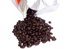 Coffee beans spilling out from a packet Stock Photos