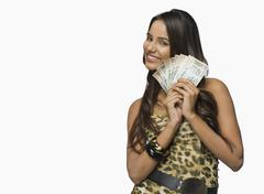 Woman holding currency notes and smiling - stock photo