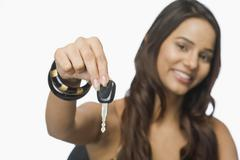 Portrait of a woman showing a car key - stock photo