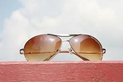 Sunglasses on pink wood and cloudy sky background Stock Photos