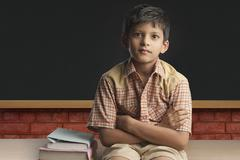 Boy imitating a teacher in a classroom Stock Photos