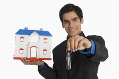 Real estate agent holding house keys and a model home Stock Photos