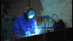 Male wearing uniform welds with welding machine torch, click for HD Stock Footage