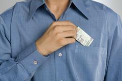 Mid section view of a man putting money in shirt pocket Stock Photos