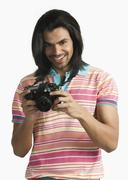 Photographer using a digital camera and smiling - stock photo