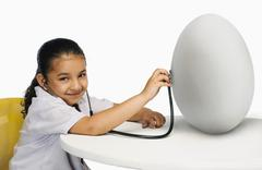 Stock Photo of Girl examining a egg with a stethoscope