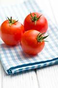 red tomatoes on napkin - stock photo