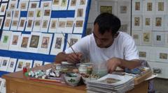 Uzbekistan, artist makes beautiful paintings, artisan in outdoor workshop Stock Footage
