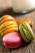 colorful macaroons on wooden table - stock photo