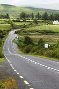 Road passing through fields, Ring Of Kerry, County Kerry, Republic of Ireland - stock photo