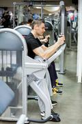 Man exercising on machines Stock Photos