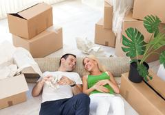 Stock Photo of couple relaxing in the middle of boxes