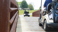 Golf Course with golf cart driving across bridge Stock Footage