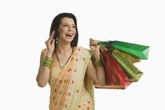 Woman talking on a mobile phone and holding shopping bags Stock Photos