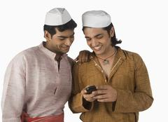 Man text messaging on a mobile phone with his friend Stock Photos