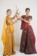 Two women performing dandiya Stock Photos