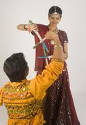 Couple performing dandiya Stock Photos