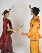 Couple performing dandiya - stock photo