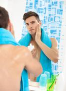 Young man applying after shave Stock Photos