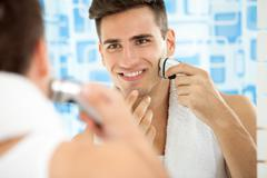 man shaving with electric shaver - stock photo