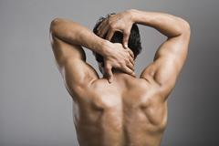 Rear view of a muscular man - stock photo