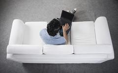 High angle view of a man sitting on a couch working on a laptop - stock photo