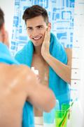 Young man applying aftershave Stock Photos