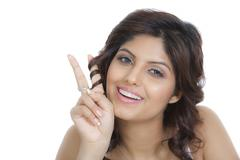 Woman smiling and showing peace sign - stock photo