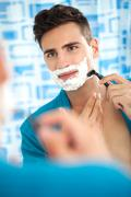 man shaving his beard - stock photo