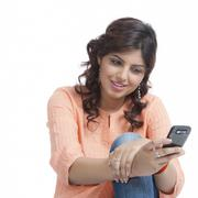 Woman text messaging on a mobile phone - stock photo