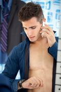 Stock Photo of busy young businessman preparing for work