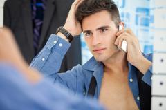 handsome men looking at himself in mirror - stock photo