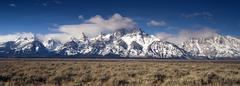 Stock Photo of jagged peaks grand teton wyoming bright sun snow clouds