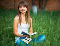 young beautiful girl with book in the park on green grass - stock photo