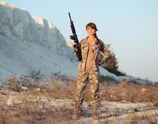 Stock Photo of female soldier dressed in a camouflage with a gun in the location