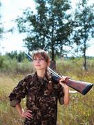 young beautiful girl with a shotgun outdoor - stock photo