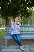 a portrait of a smiling beautiful woman in the park talking on the phone - stock photo