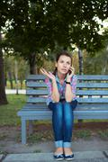 Portrait of a woman in a park on a bench talking on the phone Stock Photos
