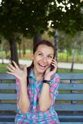 Stock Photo of a portrait of a smiling beautiful woman in the park talking on the phone