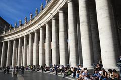 Tourists sitting on steps near columns, Berninis Column, St. Peters Square, - stock photo